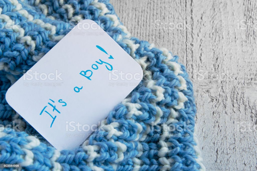 Baby shower 'It's a boy', announcement card on cozy woolen blue blanket and space for text stock photo