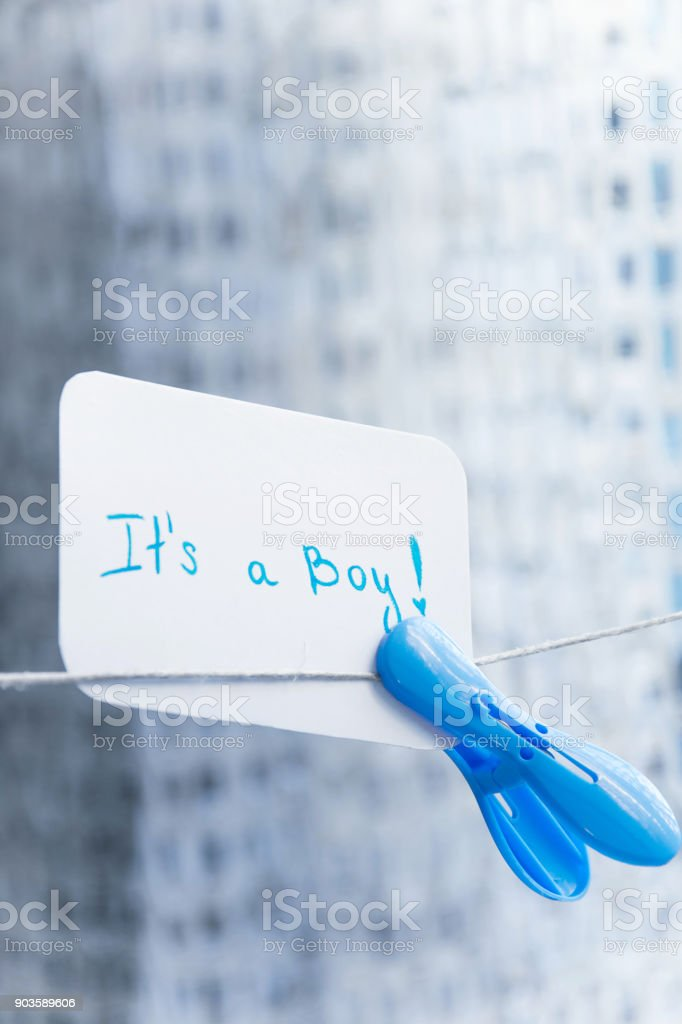 Baby shower 'It's a boy'. Simple celebration card hanging on the wire with blue clothespin and space for text. New arrival in the family stock photo