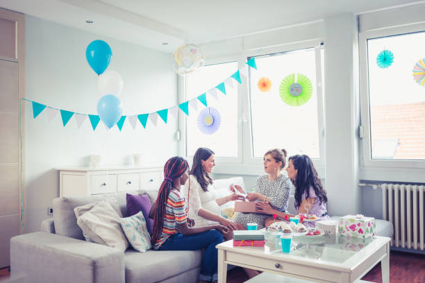 Baby shower party girls Girlfriends enjoying their time on baby shower party group of friends giving gifts to the birthday girl stock pictures, royalty-free photos & images