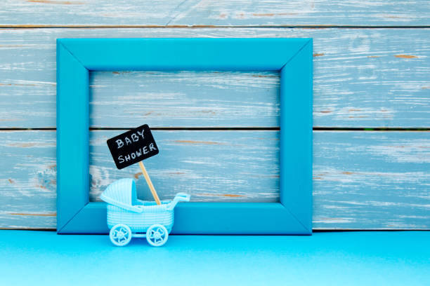 Baby Shower - toy pram with backboard sign with blue frame and wooden background stock photo