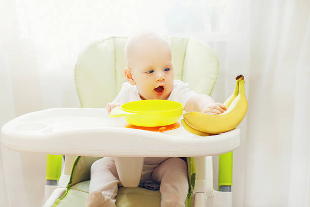 Baby am Tisch sitzend zuhause und bringt Obst Bananen – Foto