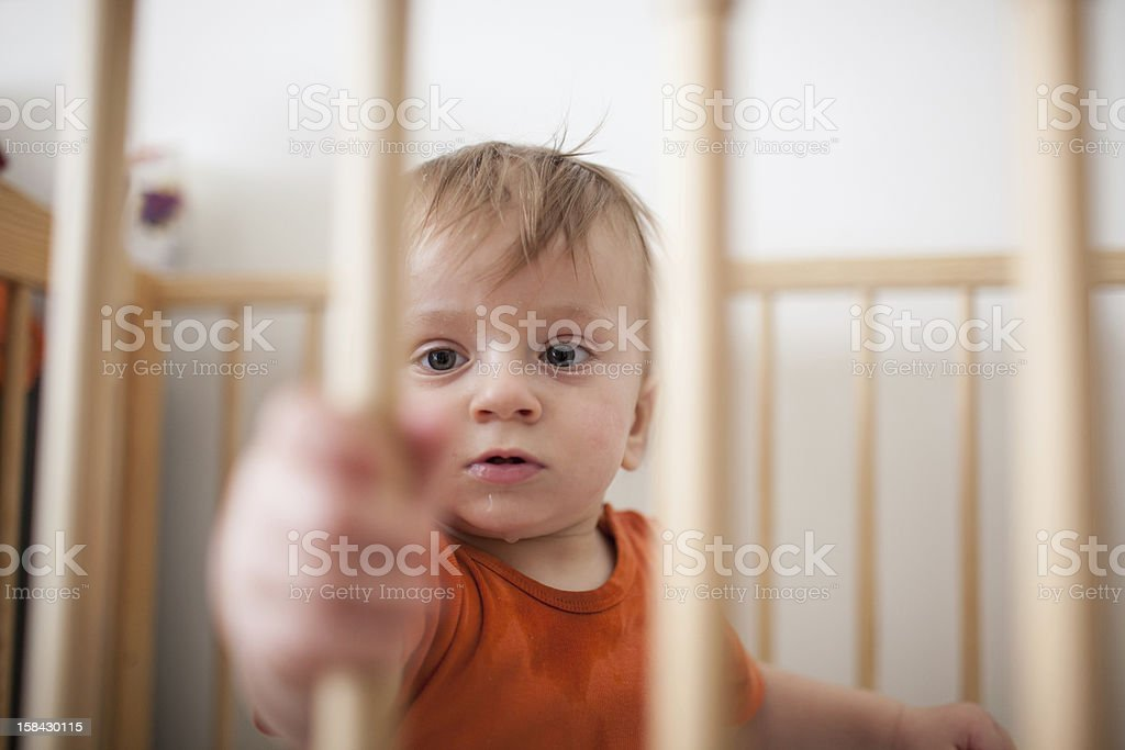 Baby sitting in a cot stock photo