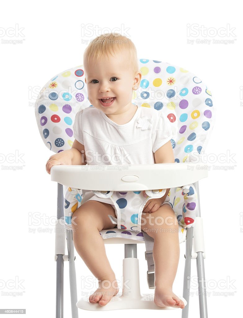 baby sitting in a high chair isolated stock photo