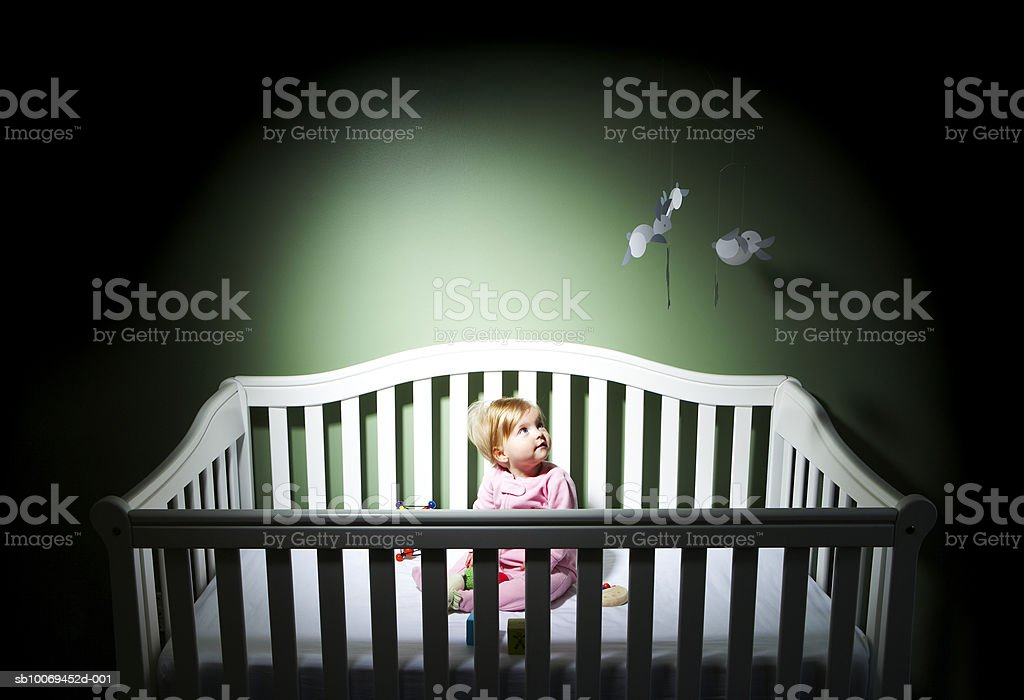 Baby (6-11 months) sitting in crib looking at hanging toys royalty-free stock photo