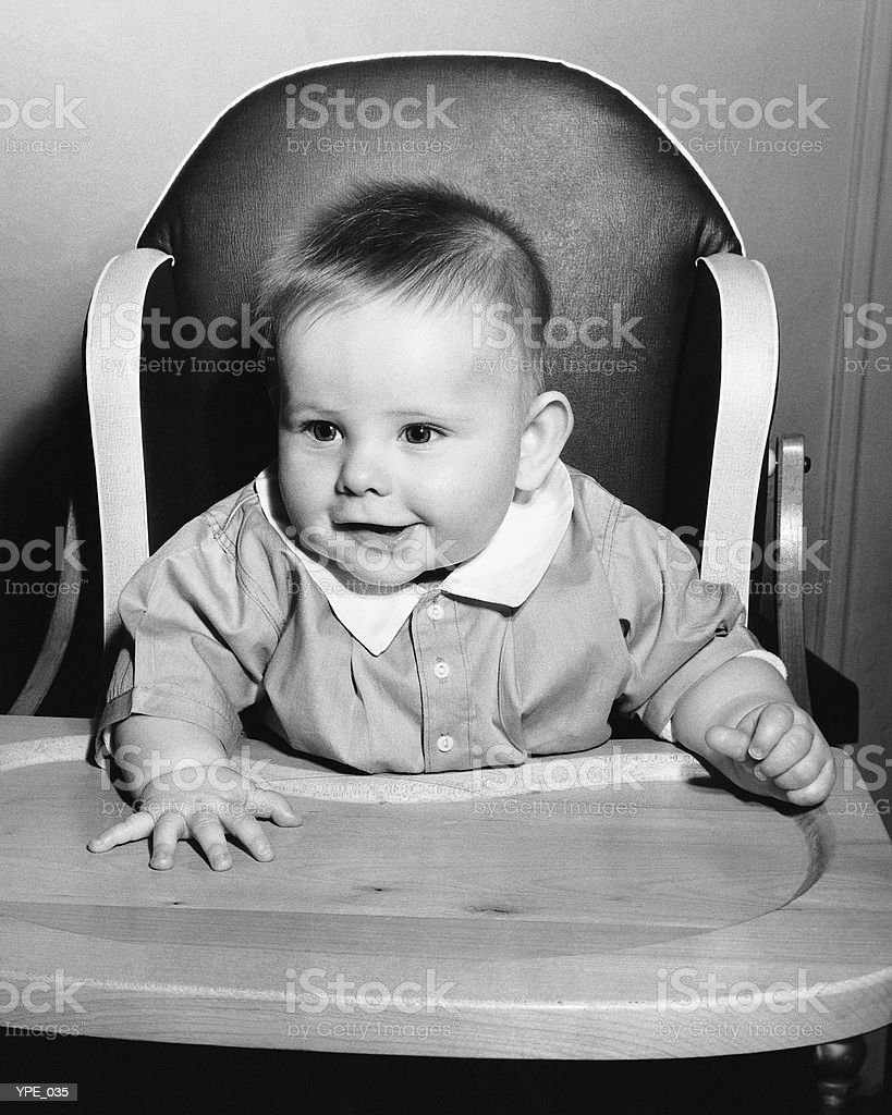Baby sitting in high chair royalty free stockfoto