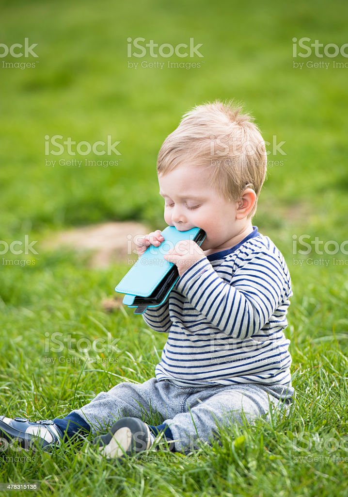 Baby sitting on a lawn and biting smart phone stock photo