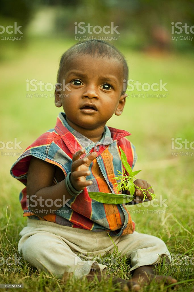 Baby sitting on grass holding green leaves and looking upward royalty-free stock photo
