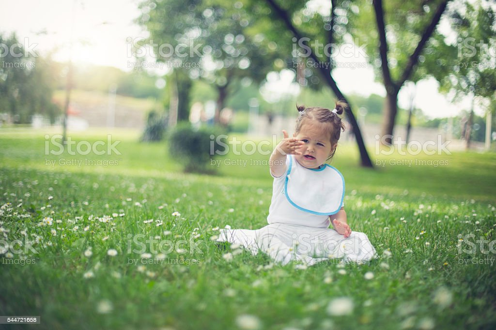 baby sitting on grass  - picking flowers stock photo