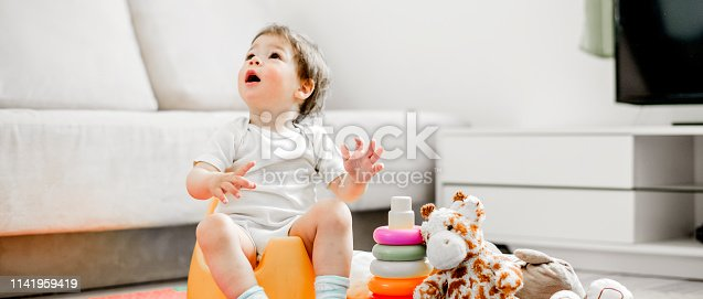 Baby Girl sitting on potty and smiling and looking up