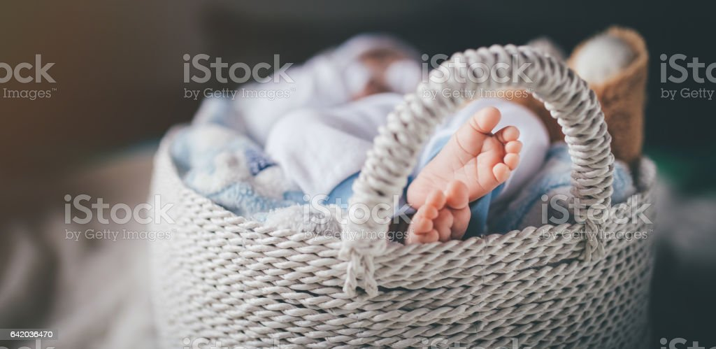 Baby sleeping in a basket stock photo