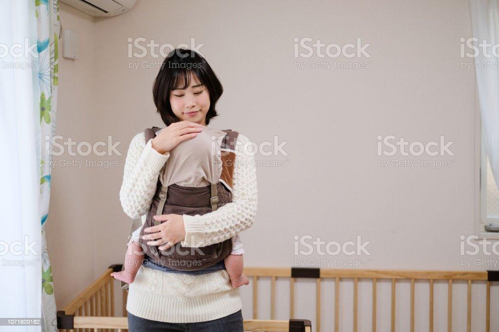 母の腕の中で眠っている赤ちゃん ストックフォト