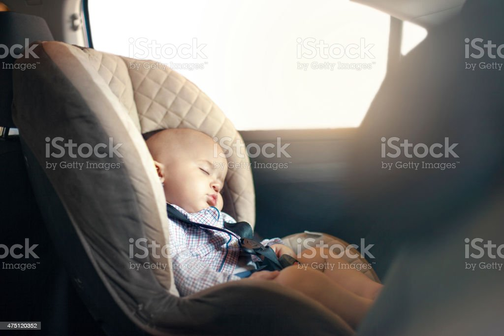 Baby sleeping in car stock photo