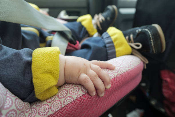 baby sleeping in car seat. No face stock photo