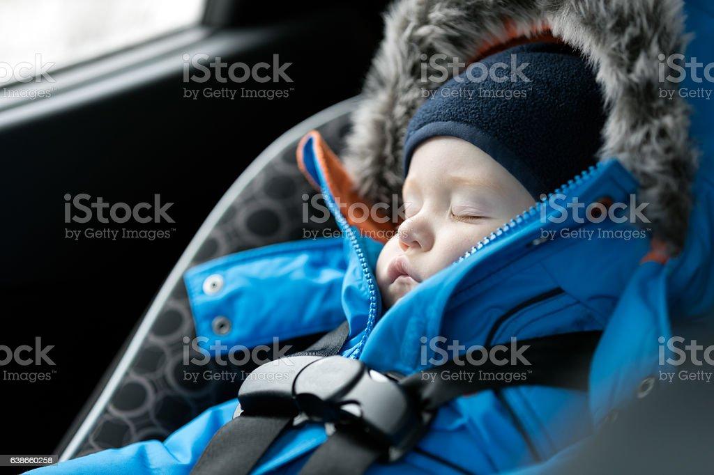Baby Sleeping in Car Seat, Winter Season stock photo