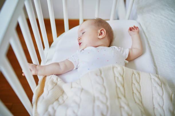 Baby schlafend in Ko-Schlaf-Krippe am Bett der Eltern befestigt – Foto