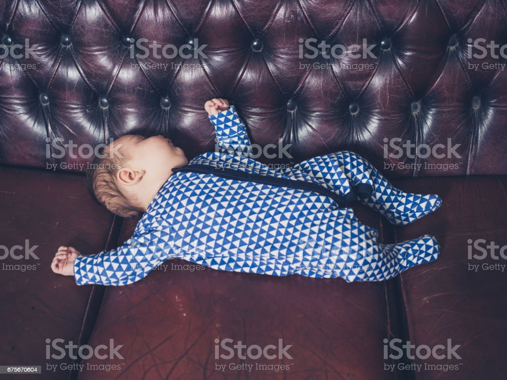 Baby sleeping on a leather sofa royalty-free stock photo