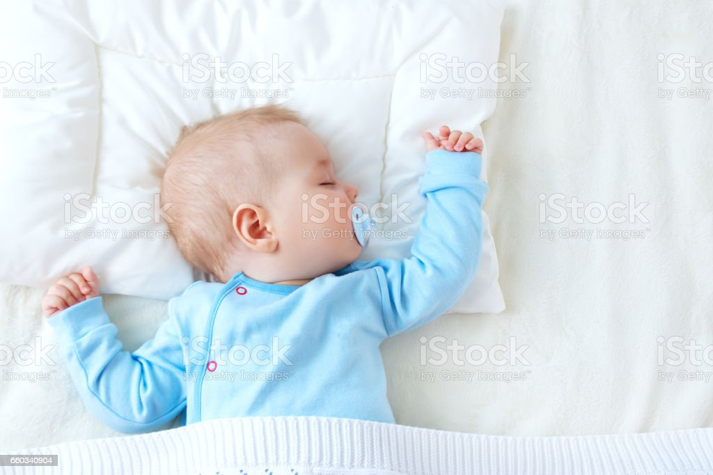 baby sleeping on blue blanket stock photo