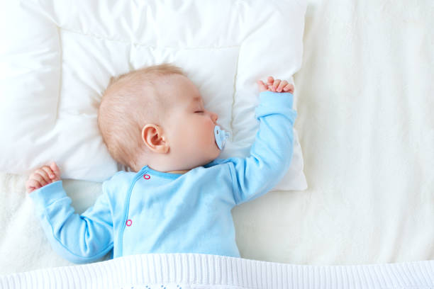 baby sleeping on blue blanket - foto stock
