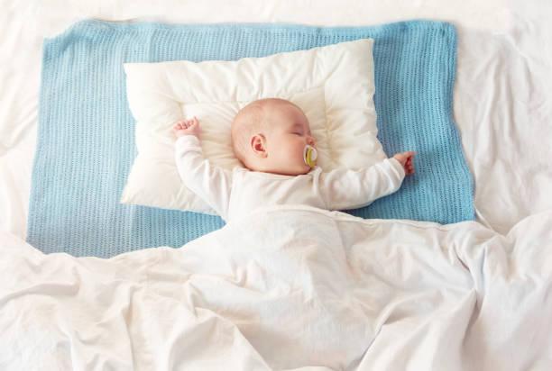 baby schlafen auf blaue decke - decke bettwäsche stock-fotos und bilder