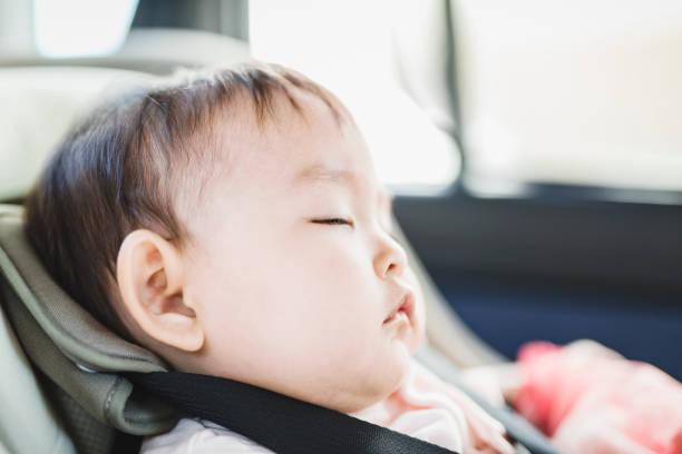 Bebê que dorme no assento da segurança da criança em um carro - foto de acervo