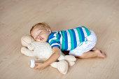 赤ちゃんグッズや牛乳瓶で床で寝ています。