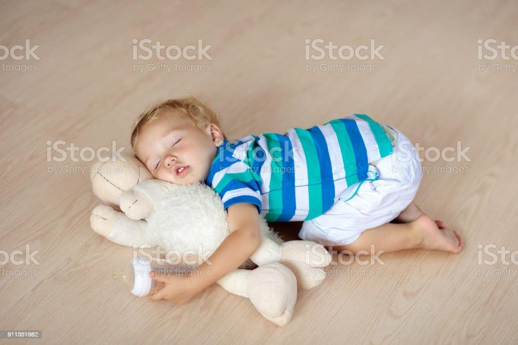 Baby sleeping on floor with toy and milk bottle. stock photo