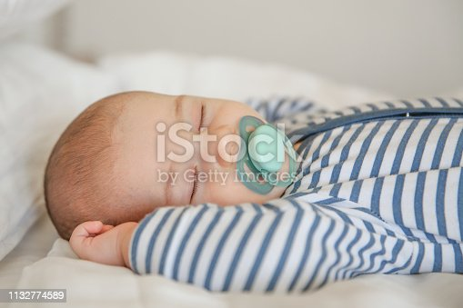 Baby sleeping on white quilt