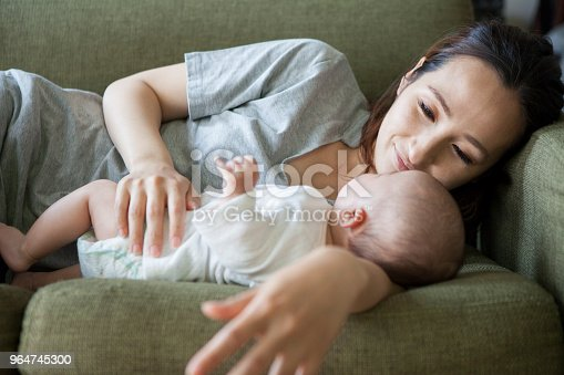 A Baby Sleeping With A Mother Who Has An Arm Pillow Stock Photo & More Pictures of Adult