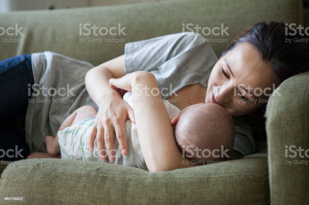A baby sleeping with a mother who has an arm pillow. royalty-free stock photo