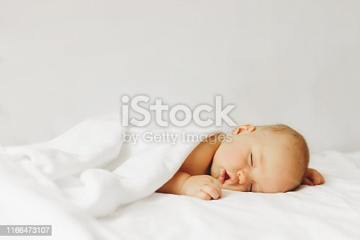 Beautiful baby sleeps on the bed in white sheets.