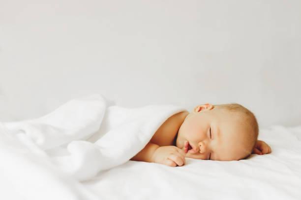 baby sleeps on the bad. - neonato foto e immagini stock