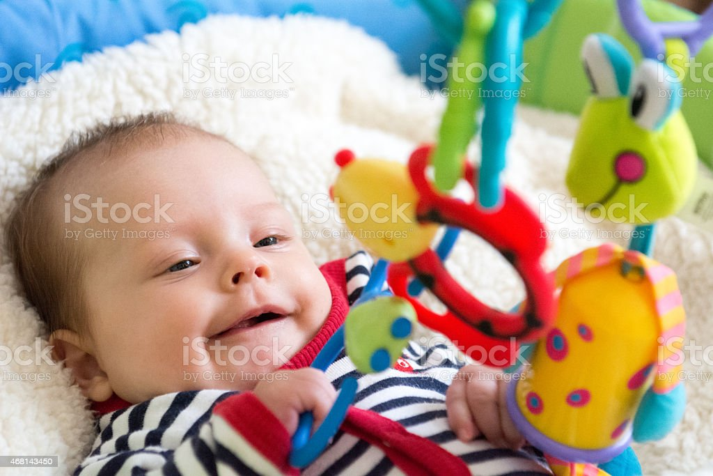 Baby smiling while playing with hanging toys on his crib stock photo