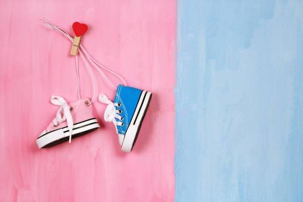 Baby sneakers on pink and blue background, boy or girl concept stock photo