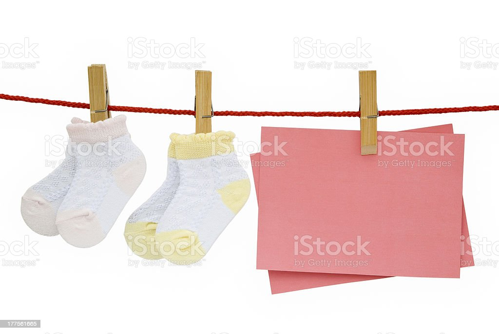baby socks and blank note hanging with clipping path stock photo