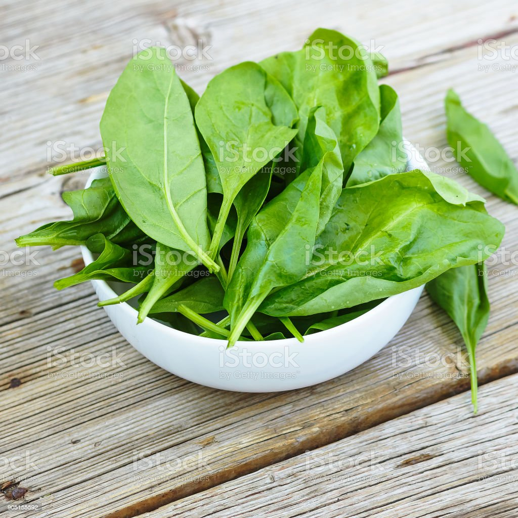 Baby spinach in a white bowl on a wooden board. Healthy food. Detox. Summer time stock photo