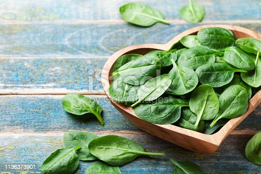 Baby spinach leaves in bowl on rustic wooden table. Organic and healthy food.