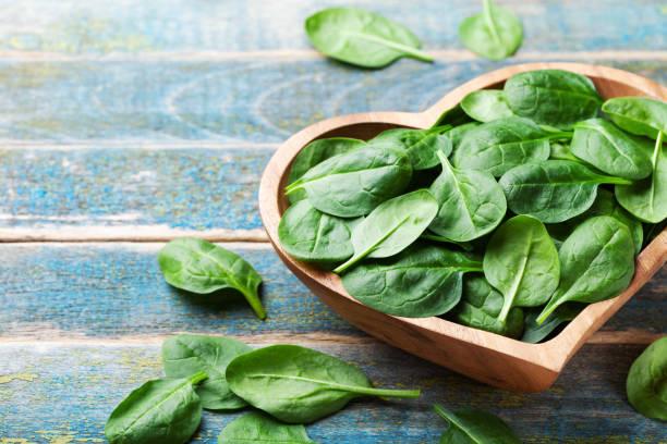baby spinach leaves in bowl on wooden table. organic and healthy food. - szpinak zdjęcia i obrazy z banku zdjęć
