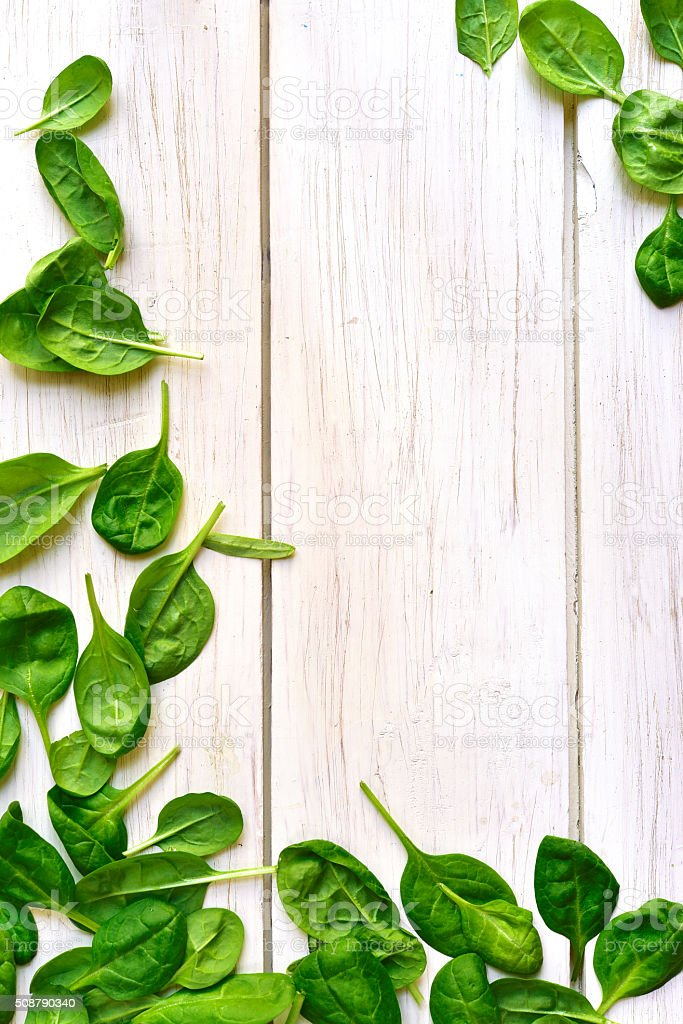 Baby spinach leaves on a white wooden table. stock photo