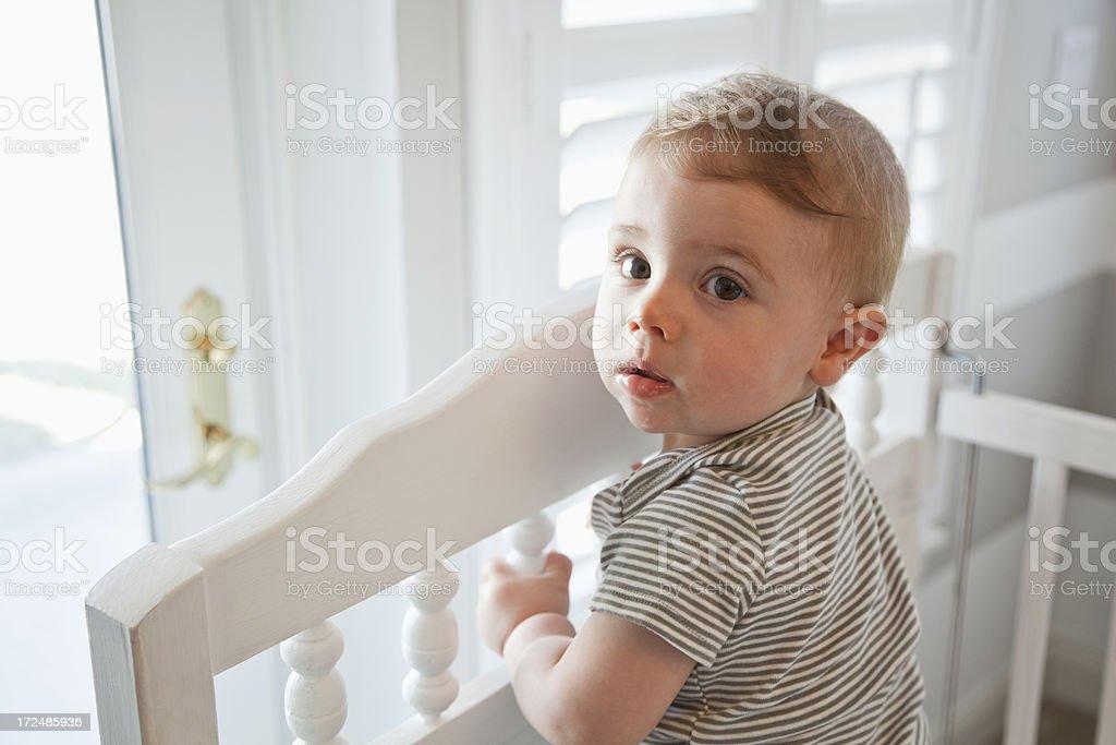 Baby standing in crib stock photo
