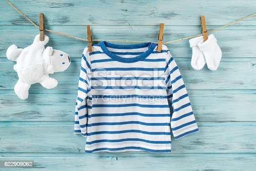 istock Baby striped shirt, socks and white toy bear on clothesline 622909062