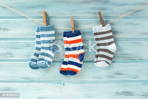istock Baby striped socks on a clothesline on wooden background 623095444