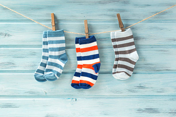 Baby striped socks on a clothesline on wooden background stock photo