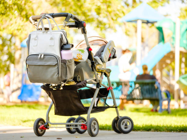 Baby Stroller and Diaper Bag A baby stroller with a diaper bag at the park. baby carriage stock pictures, royalty-free photos & images