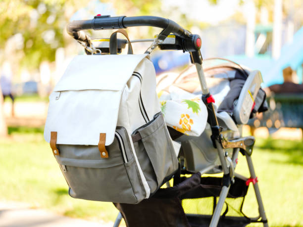 Baby Stroller and Diaper Bag A baby stroller with a diaper bag at the park. baby stroller stock pictures, royalty-free photos & images