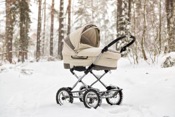 Baby stroller in winter forest. tire tracks on snow. Infant baby sleep inside the pram on fresh air stock photo