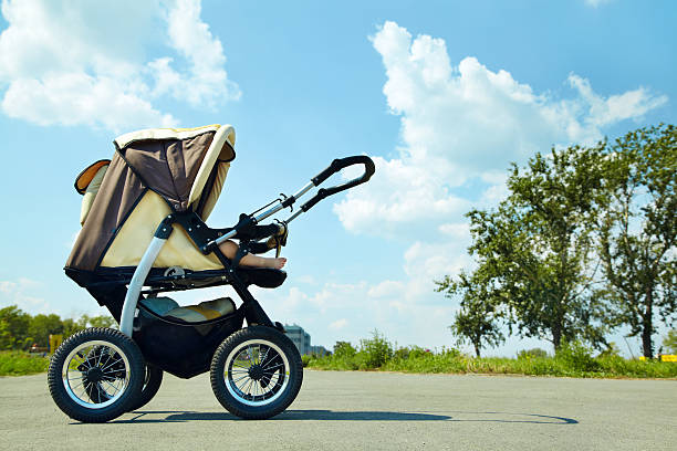 baby stroller baby stroller on a walk in the park summer day baby carriage stock pictures, royalty-free photos & images