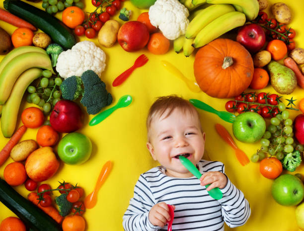 Baby surrounded with fruits and vegetables stock photo