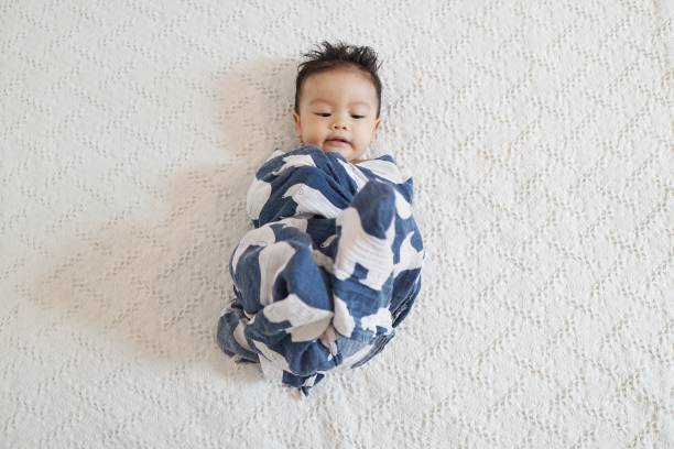 Baby swaddled with a blue blanket A picture of an adorable boy looks unhappy being swaddled like a small baby, with a white background. baby blanket stock pictures, royalty-free photos & images