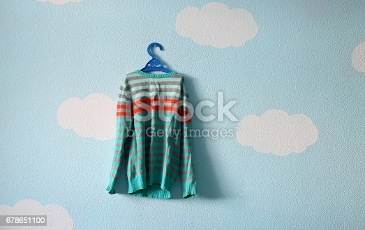 678651100 istock photo Baby sweater on the beautiful blue wallpaper 678651100