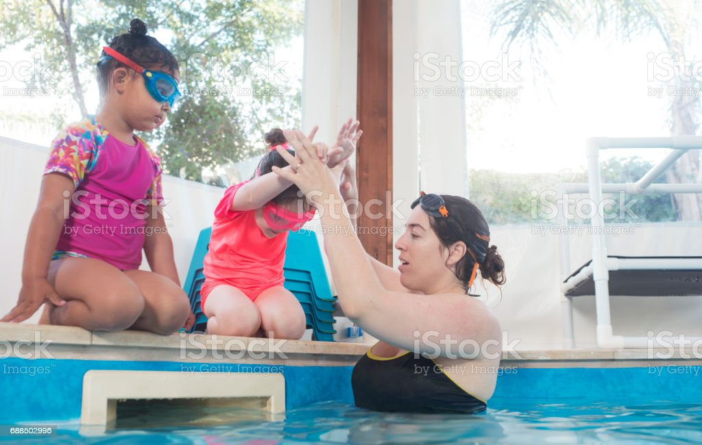 Swimming trainer guiding baby kids to headfirst jump, holding kid\'s...
